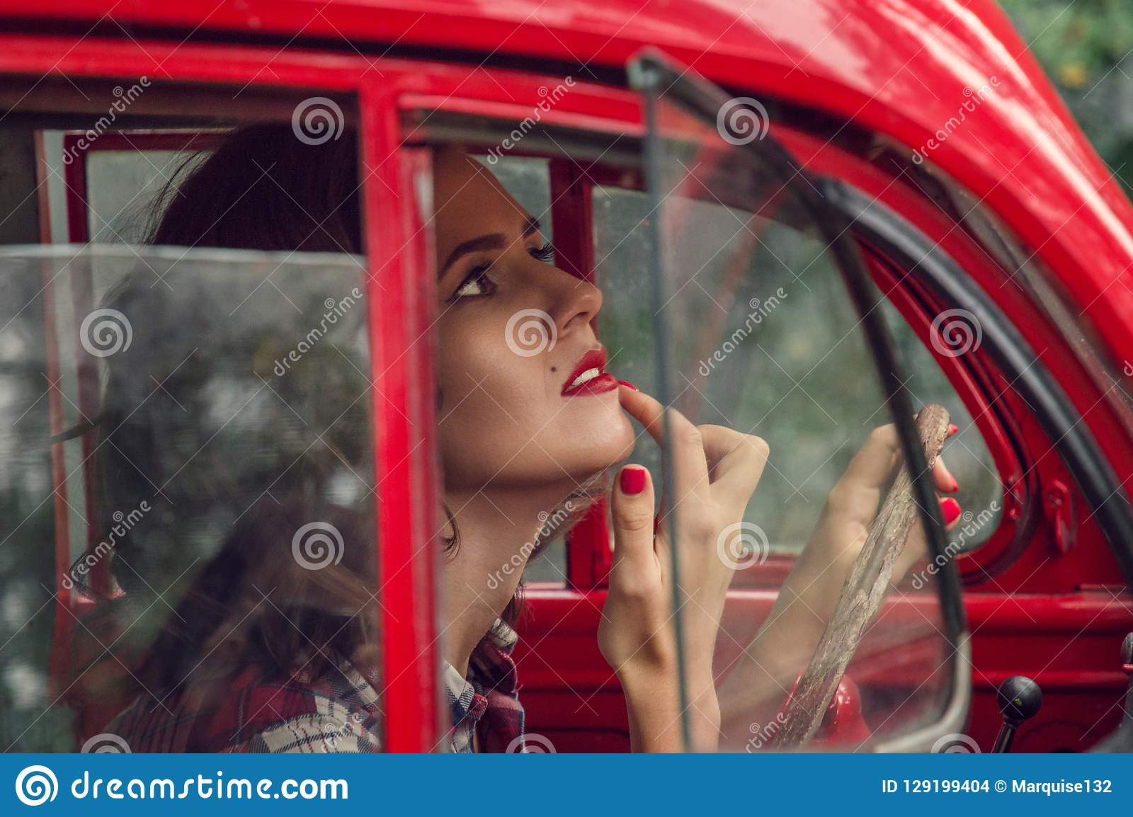 A beautiful pin-up girl in a plaid shirt corrects make-up in the salon of an old red retro car.