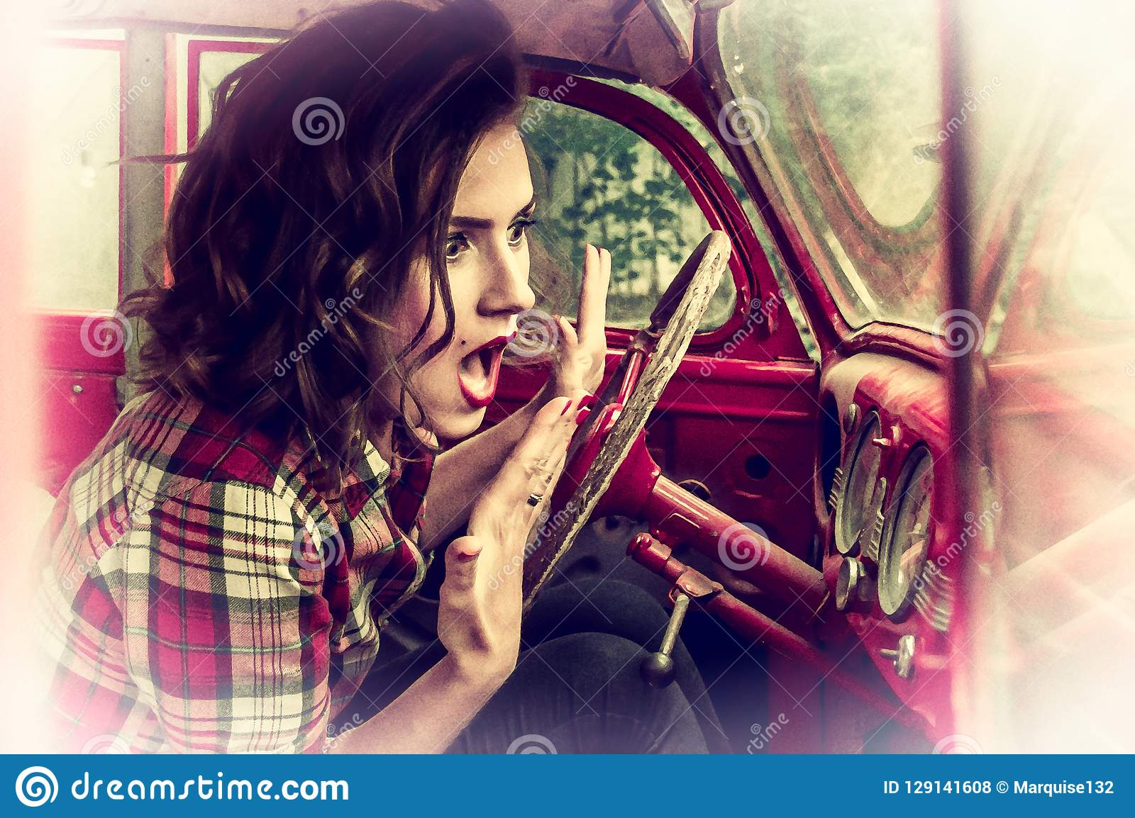 Beautiful pin-up girl in a plaid shirt is frightened and screaming, looking at the speedometer in the cabin of