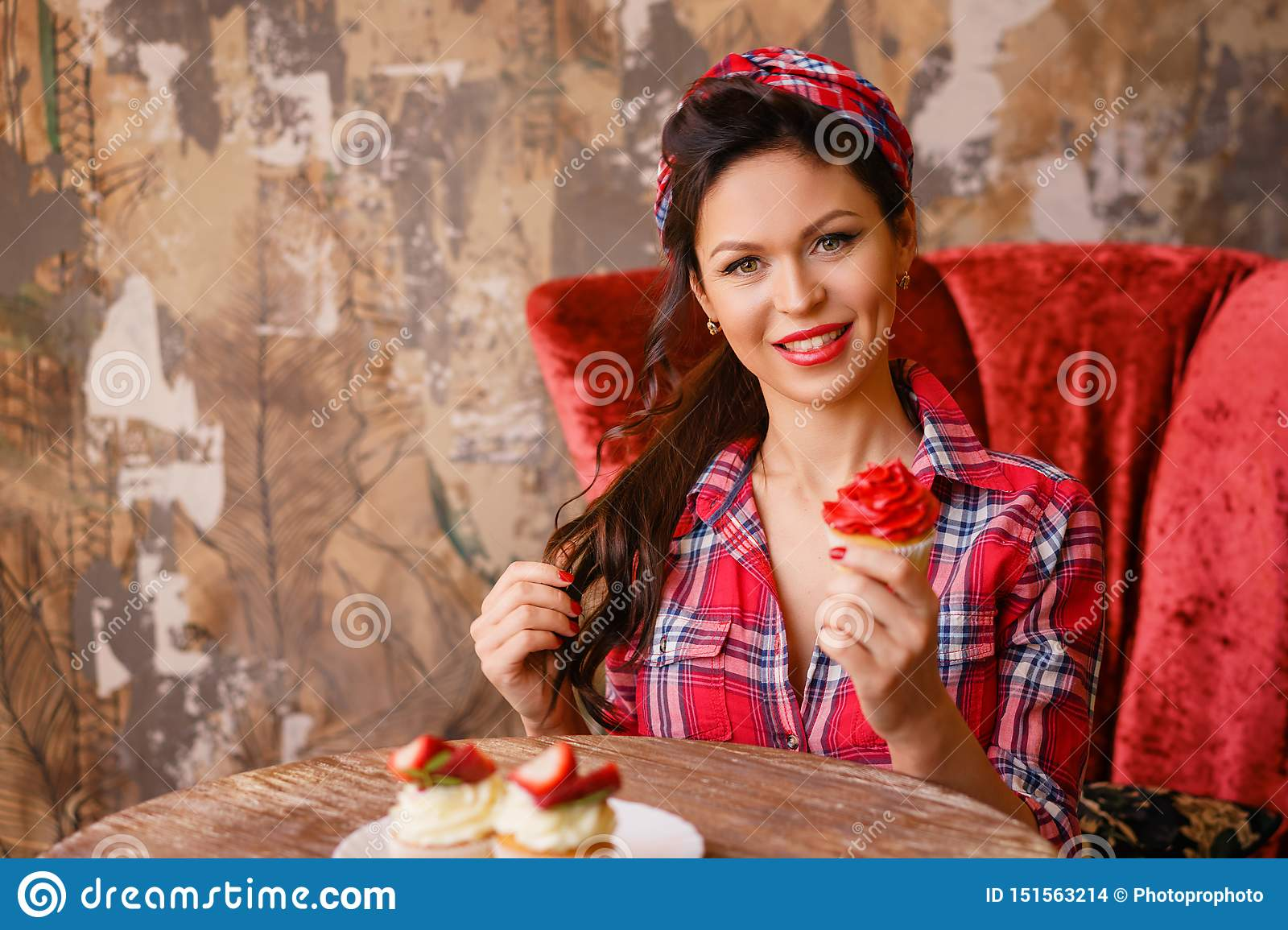 Beautiful pin-up woman sitting at a table in a cafe