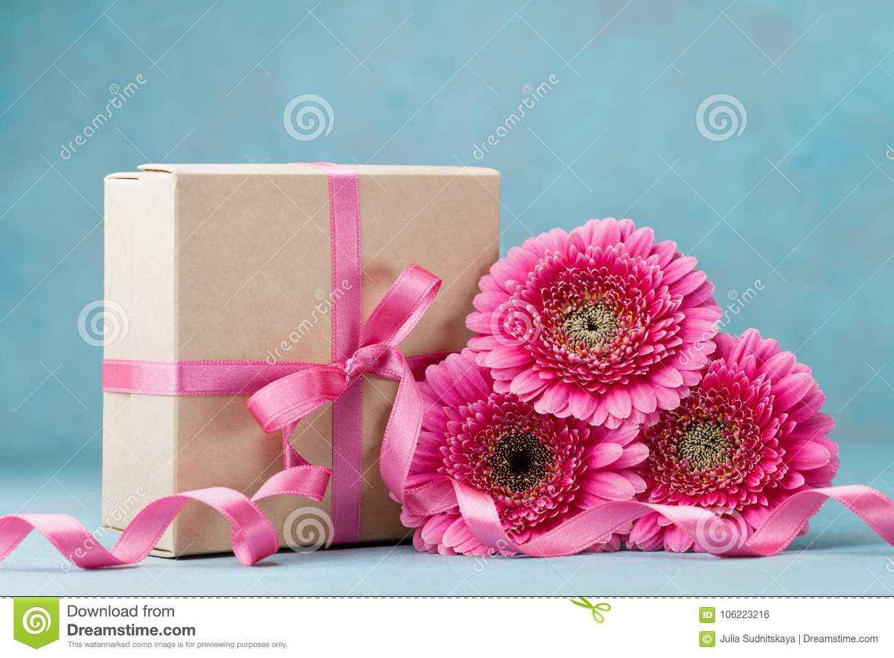 Beautiful pink gerbera flowers and gift box with ribbon on turquoise beautiful pink gerbera flowers and gift box with ribbon on turquoise table greeting card for birthday woman or mothers day stock photo image of desk izmirmasajfo