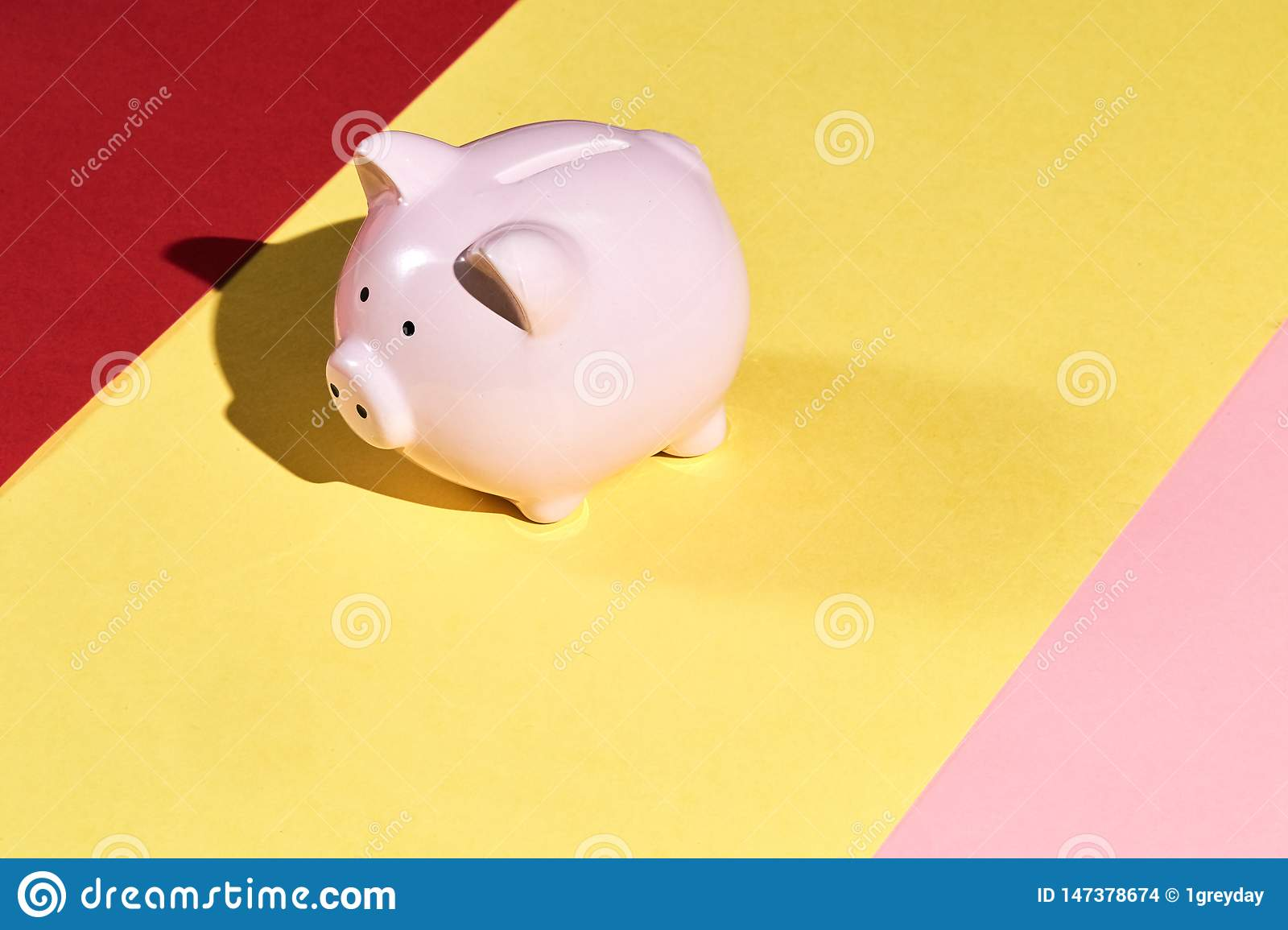 Beautiful pink piggy bank isolated on yellow, pink and red background