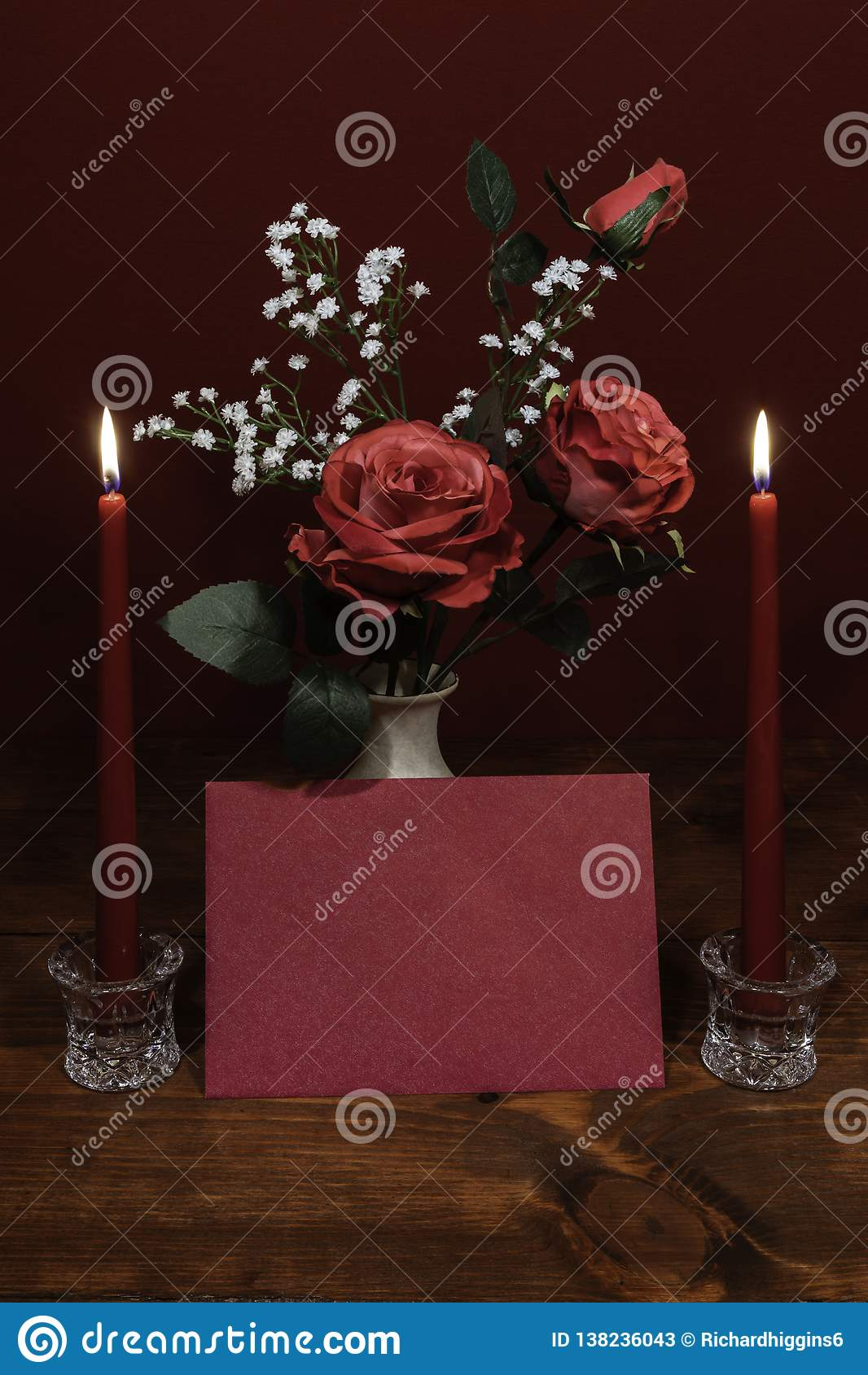 Beautiful pink roses in a vase accented with Baby`s Breath flowers, Two lit ed candles in crystal holder and a card.