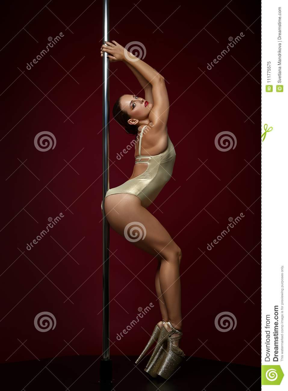 Beautiful pole dancer in golden bodywear on pylon
