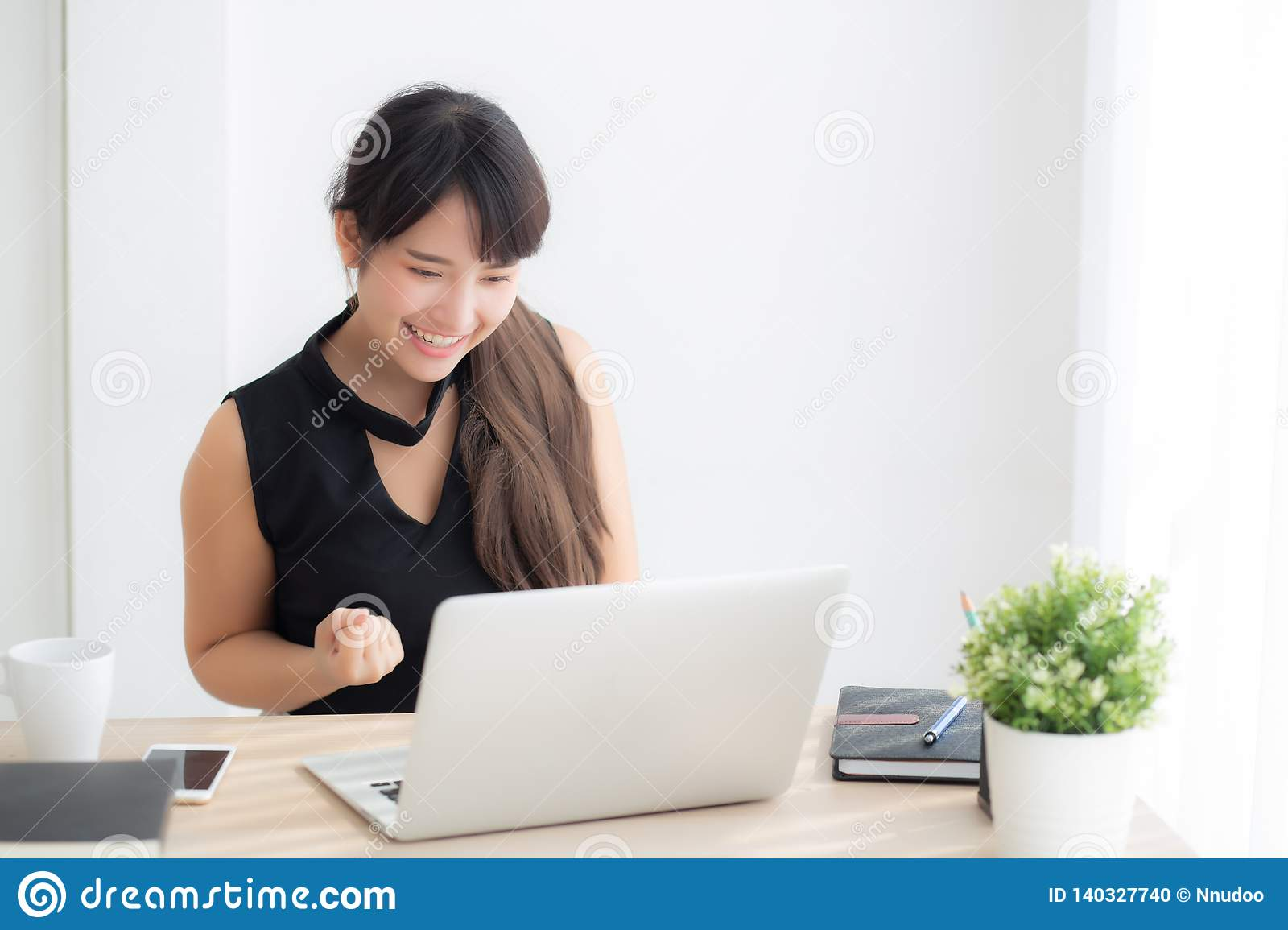Beautiful portrait asian young woman smile working online laptop computer with happy satisfied sitting on desk office