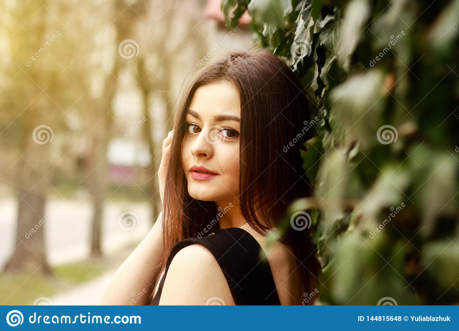 Portrait of thoughtful young pretty woman at street
