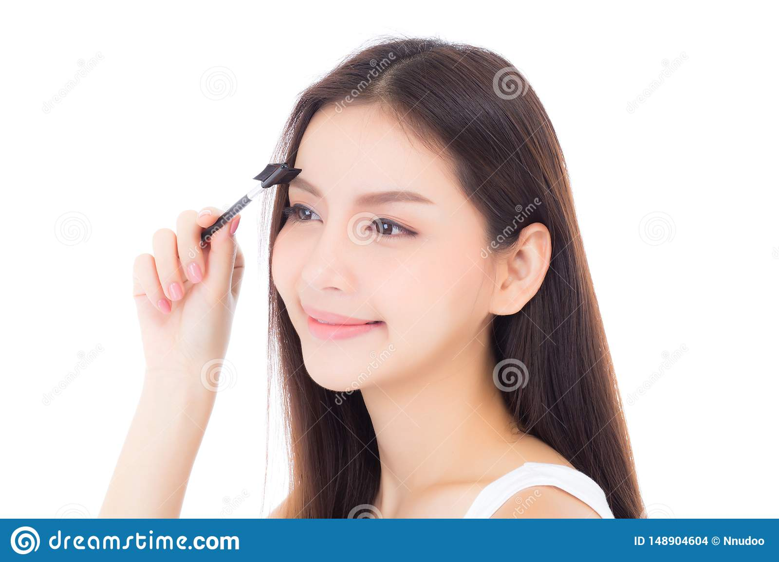 Beautiful portrait young asian woman applying eyebrow or eyelash with makeup brush isolated on white background
