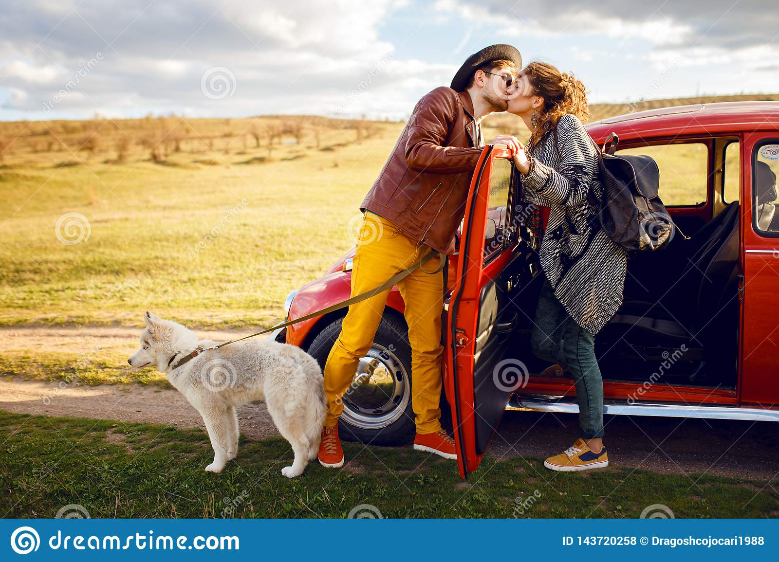 Beautiful portrait of young couple, near vintage red car, with their husky dog, isolated on a nature background.