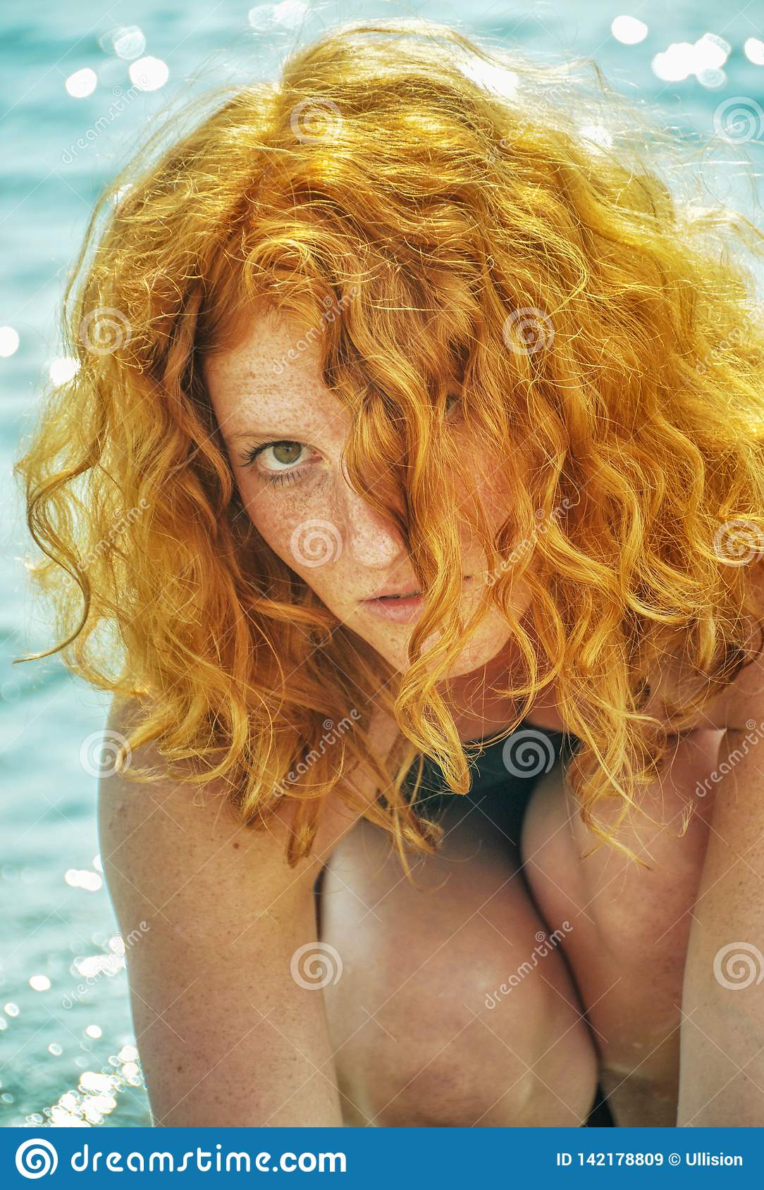 Beautiful portrait of a young elegant sexy red-haired curly woman sitting at the beach