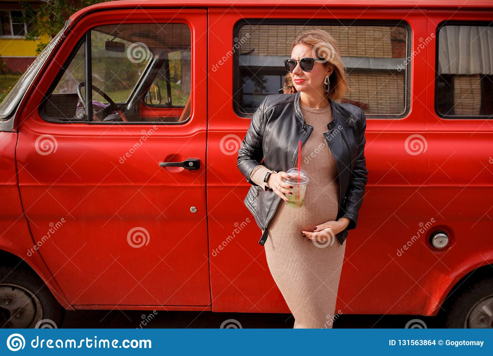 Beautiful pregnant girl is walking. Pregnant girl is standing on the street and dreaming. Hipster trendy pregnancy girl