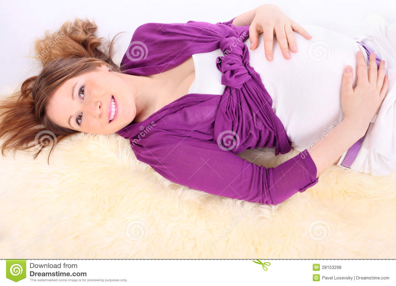 Beautiful pregnant woman lies on white fur