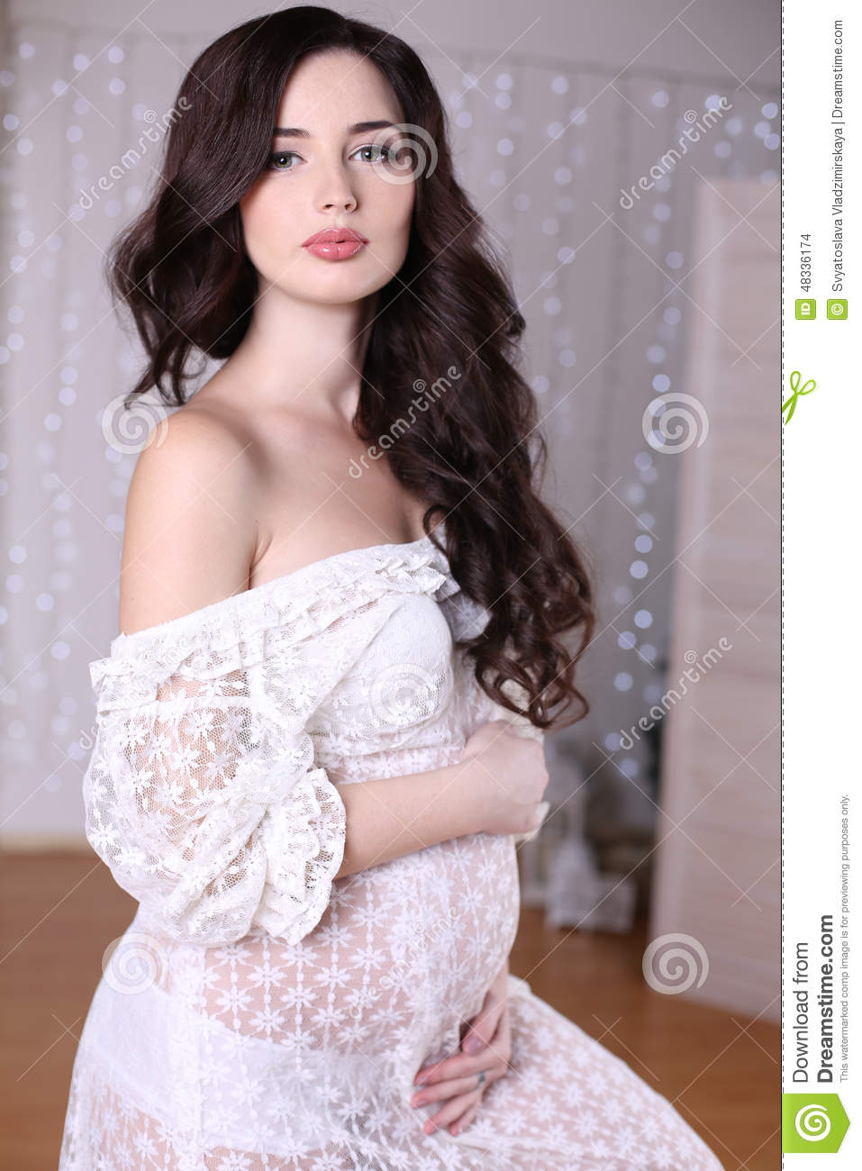 beautiful pregnant woman with long dark hair wearing lace