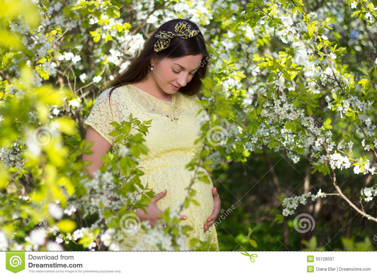 Beautiful pregnant woman posing in blooming cherry garden for Gardening while pregnant