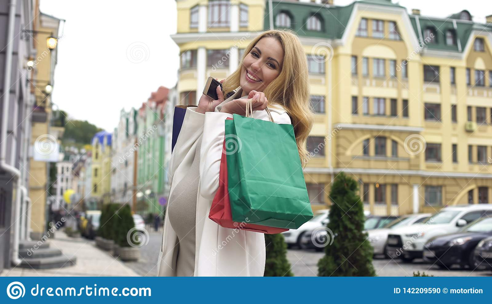 Beautiful pregnant woman smiling in camera, holding shopping bags and smartphone