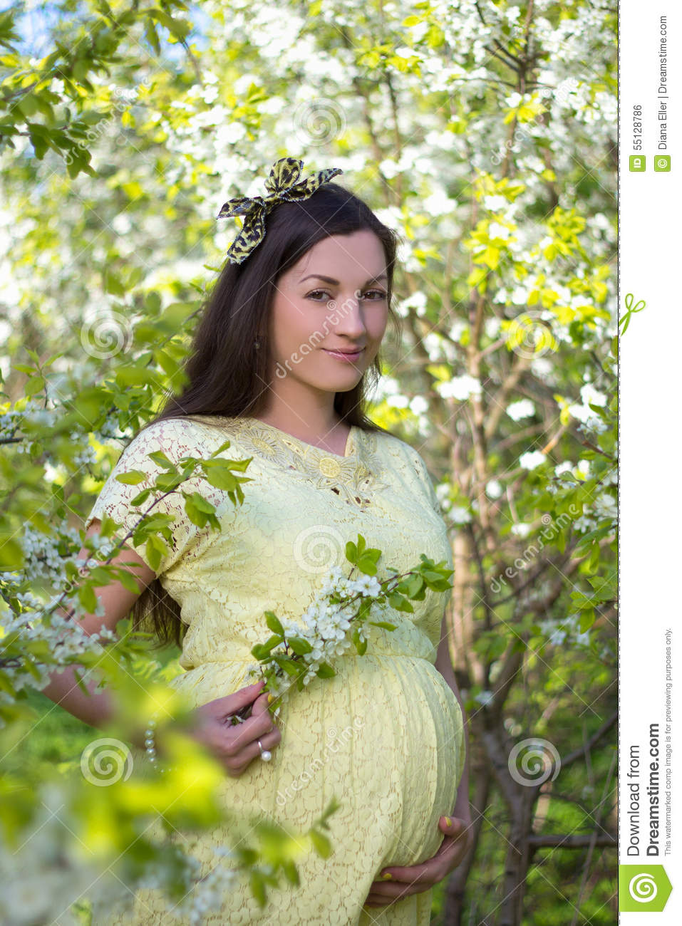 Beautiful pregnant woman walking in blooming spring garden for Gardening while pregnant