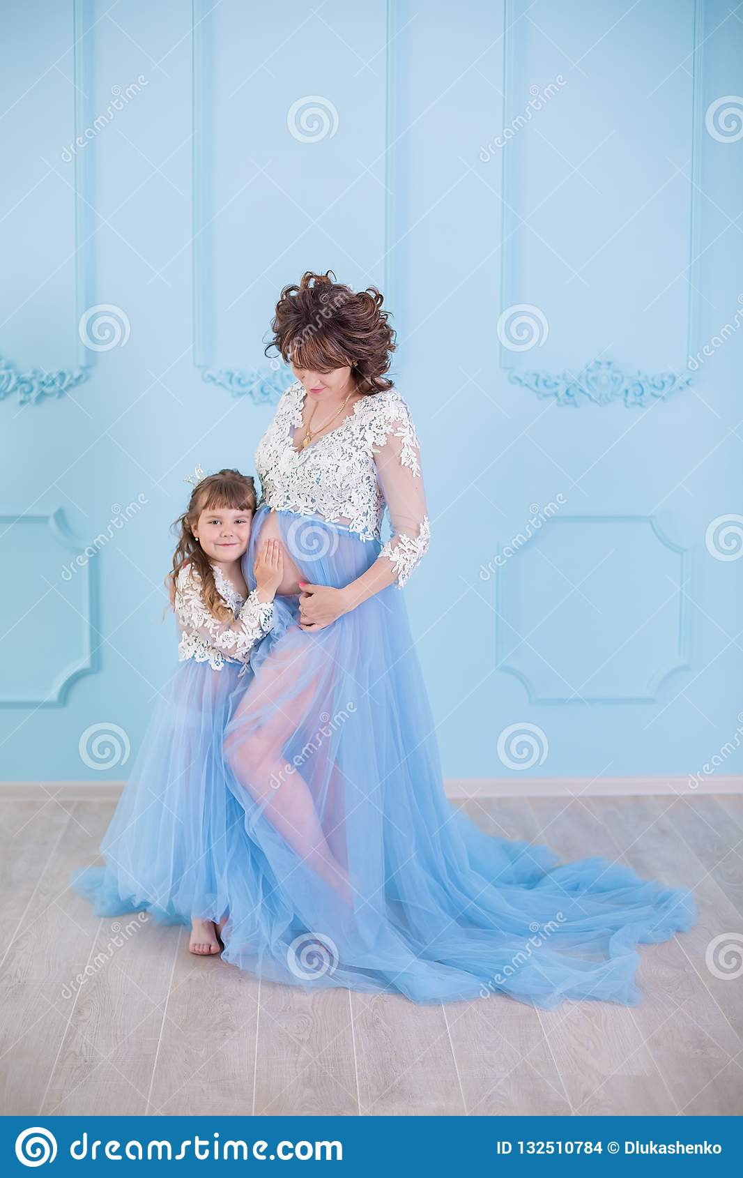 11a36ce177f Beautiful pregnant woman wearing long blue luxury dress with daughter  posing in studio with happy lovely