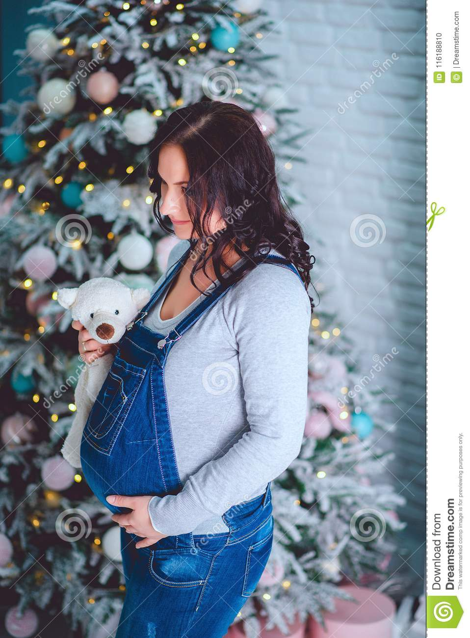 A beautiful pregnant young girl in a blue denim overalls holds a bear in her hands and looks at him