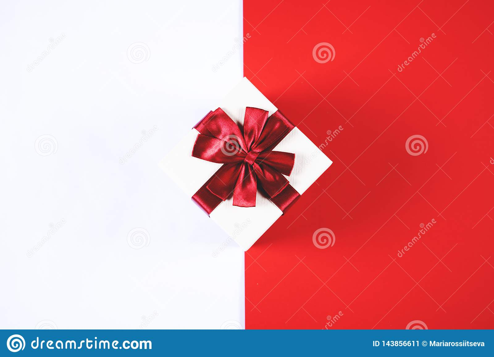 Beautiful present box on red and white background