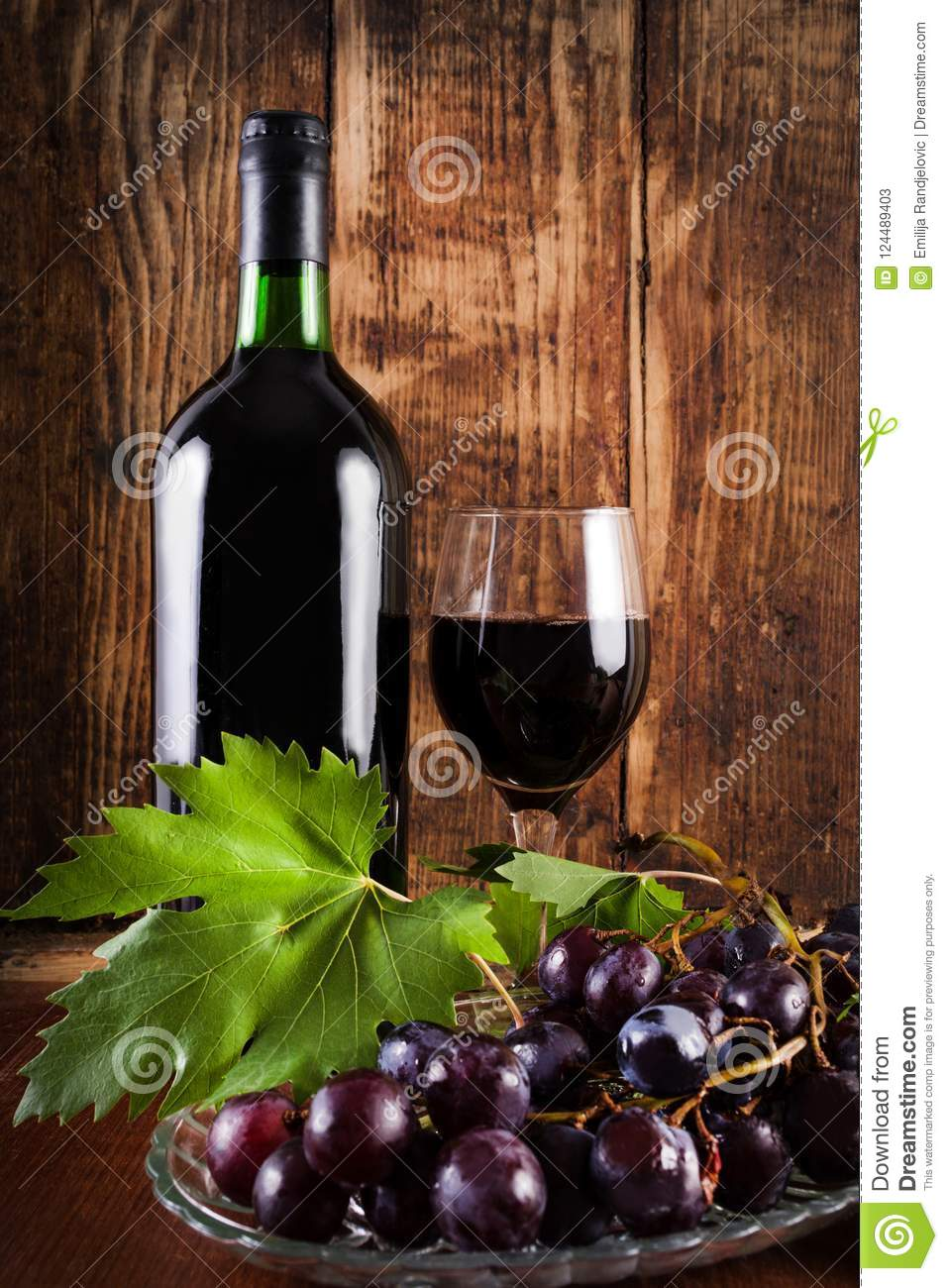 Red Grape On Plate With Vine Decoration And Glass And Bottle