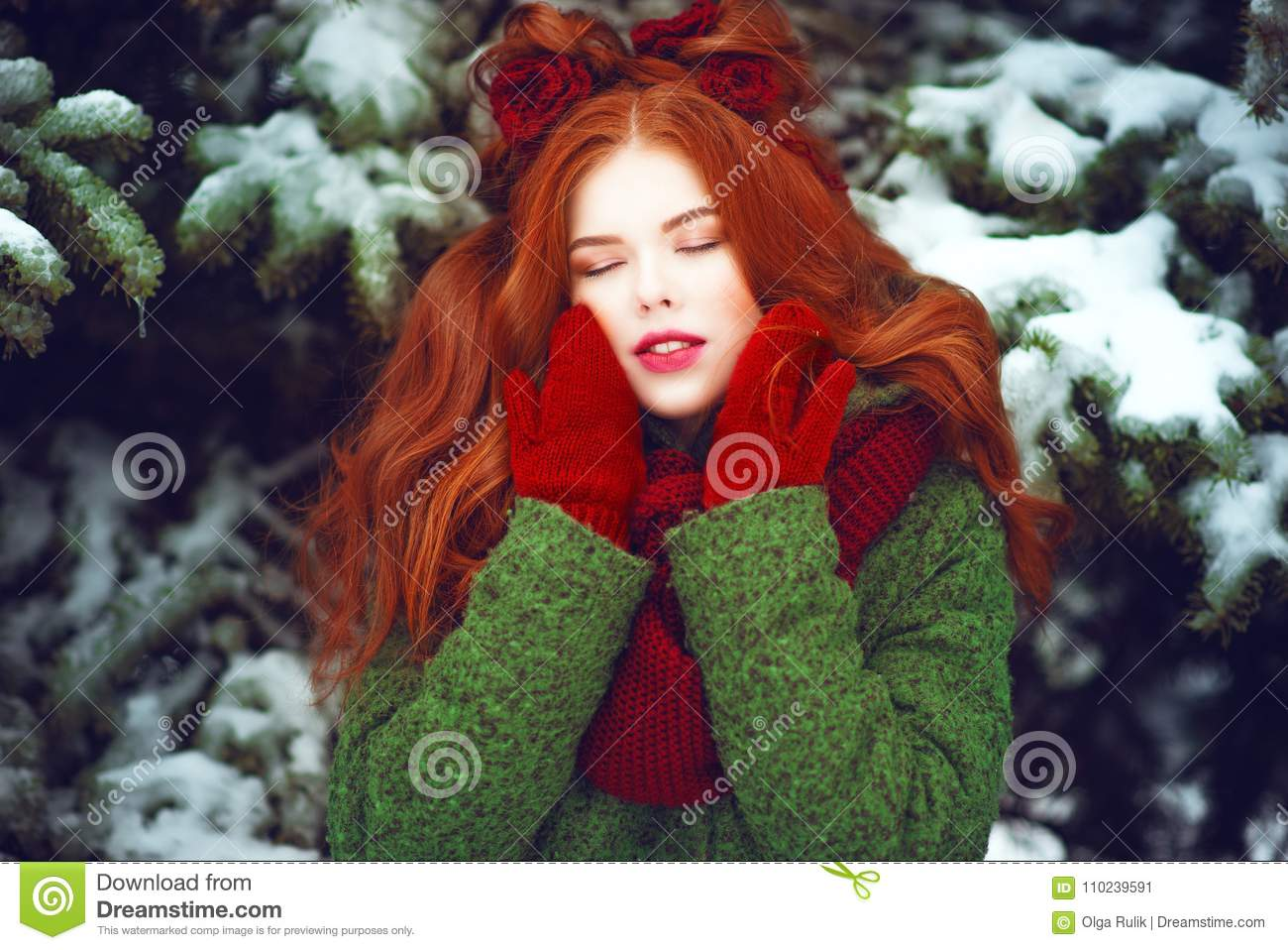 Beautiful red haired girl with creative hairstyle posing with closed eyes in front of snow covered firtrees