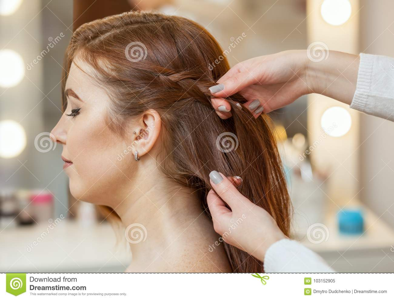 Beautiful, red-haired girl with long hair, hairdresser weaves a French braid,