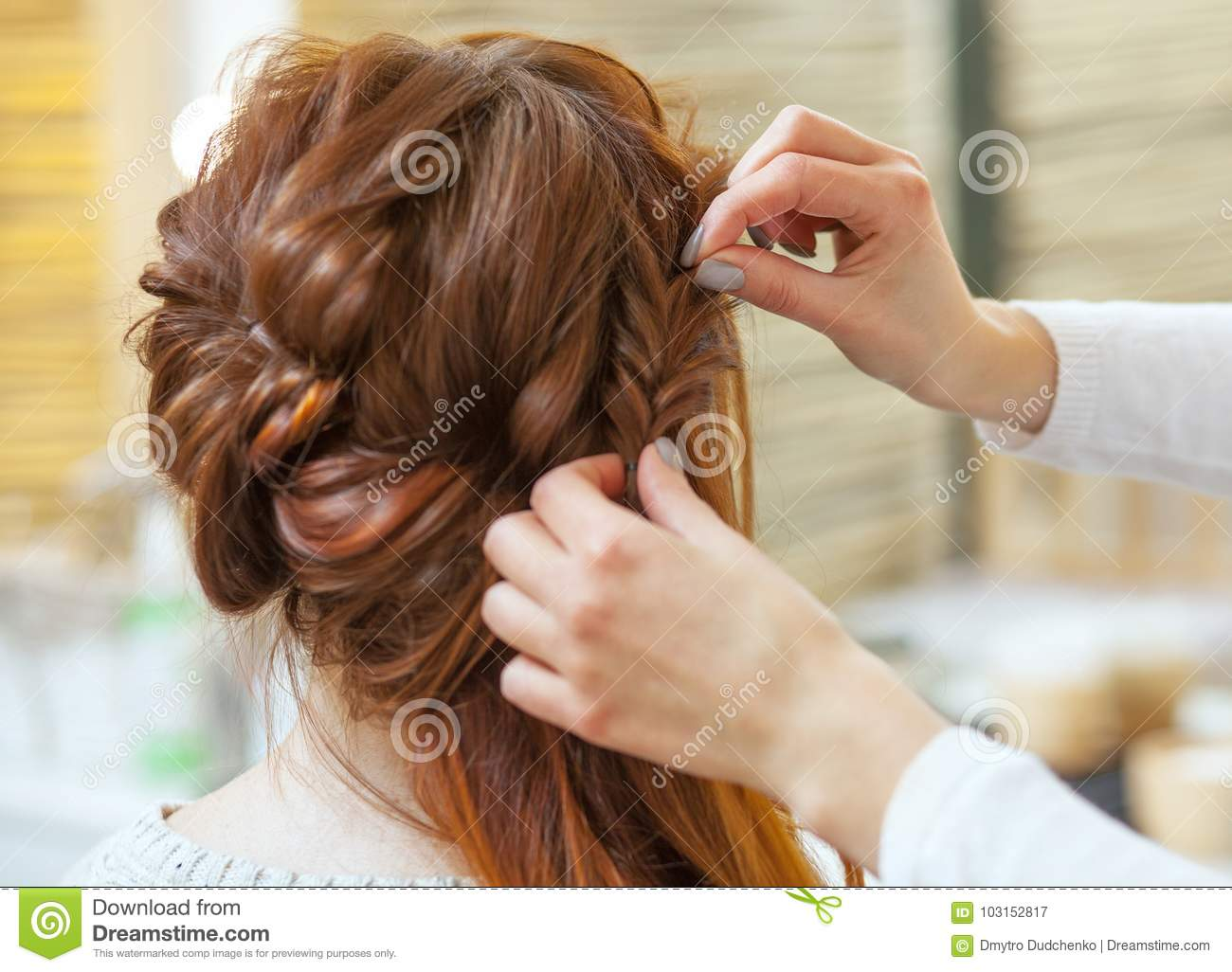 Beautiful, red-haired girl with long hair, hairdresser weaves a French braid, in a beauty salo