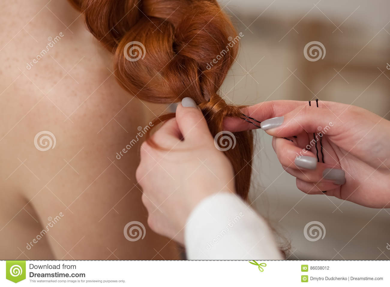 Beautiful, red-haired girl with long hair, hairdresser weaves a French braid, in a beauty salon.
