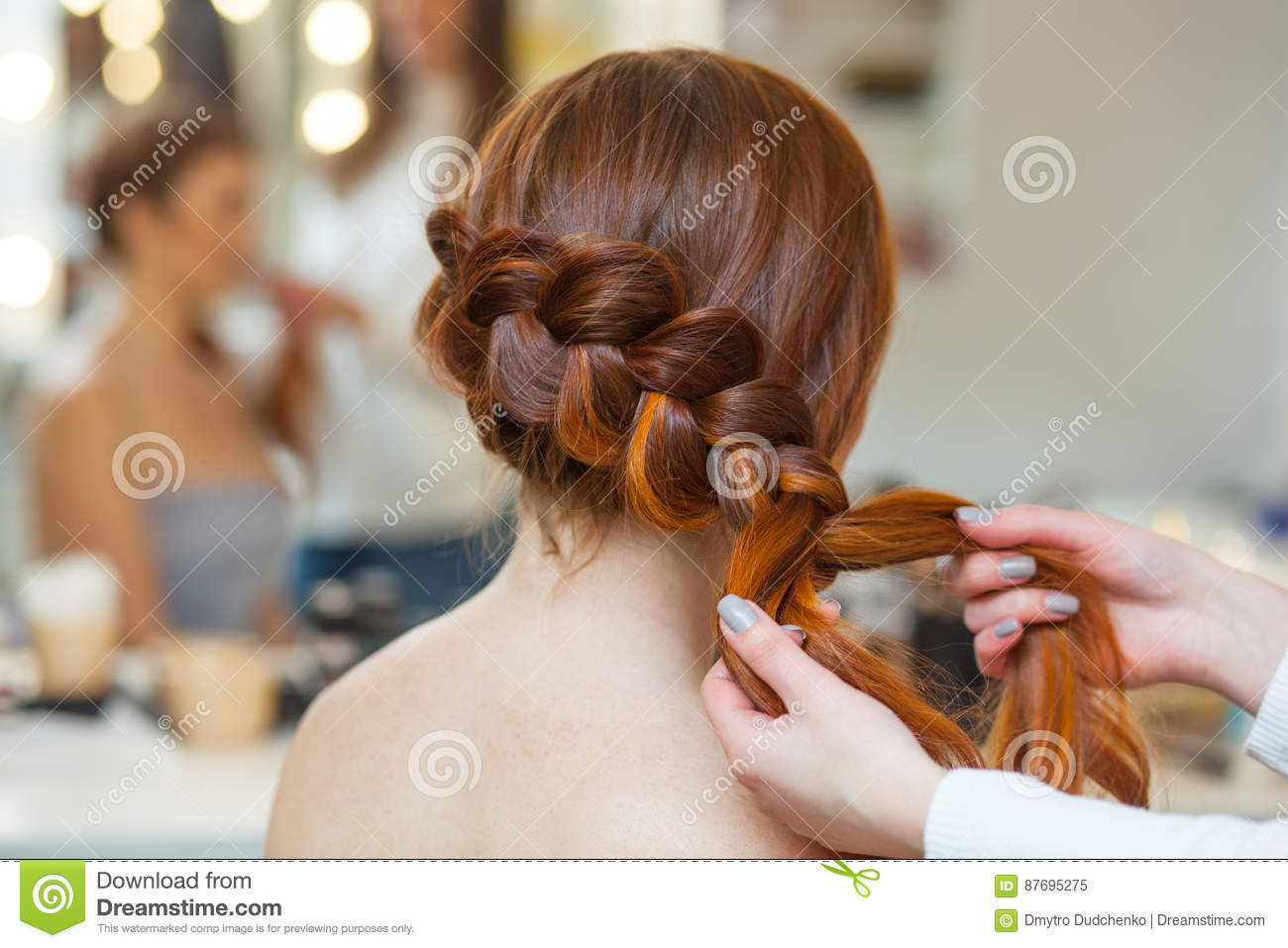 Beautiful red-haired hairy girl, hairdresser weaves a French braid, close-up in a beauty salon.