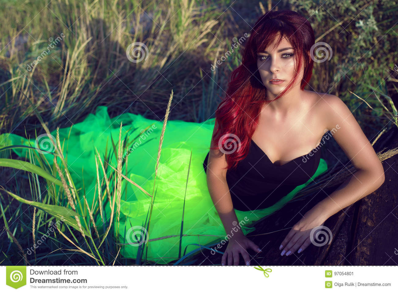 Beautiful red haired woman in black corset and long tail green veiling skirt leaning on the shabby upside down wooden boat