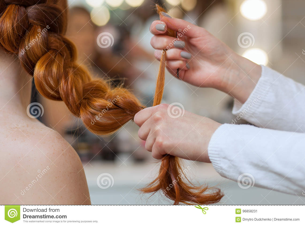 Beautiful, red hairy girl, hairdresser weaves a French braid, close-up in a beauty salon.