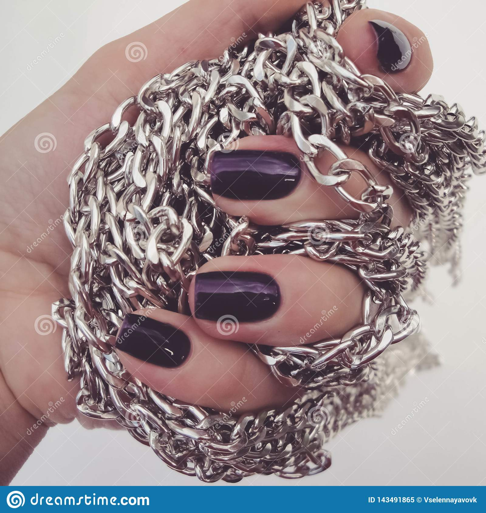 Beautiful red nails and chain close up.Beautiful, well-groomed nails with purple nail polish and chain in hand