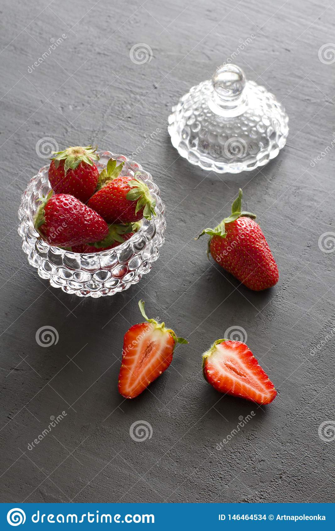 Beautiful red strawberry in glass round bowl. Strawberries on a black dark concrete background. Rustic style. Vertical. Minimalism