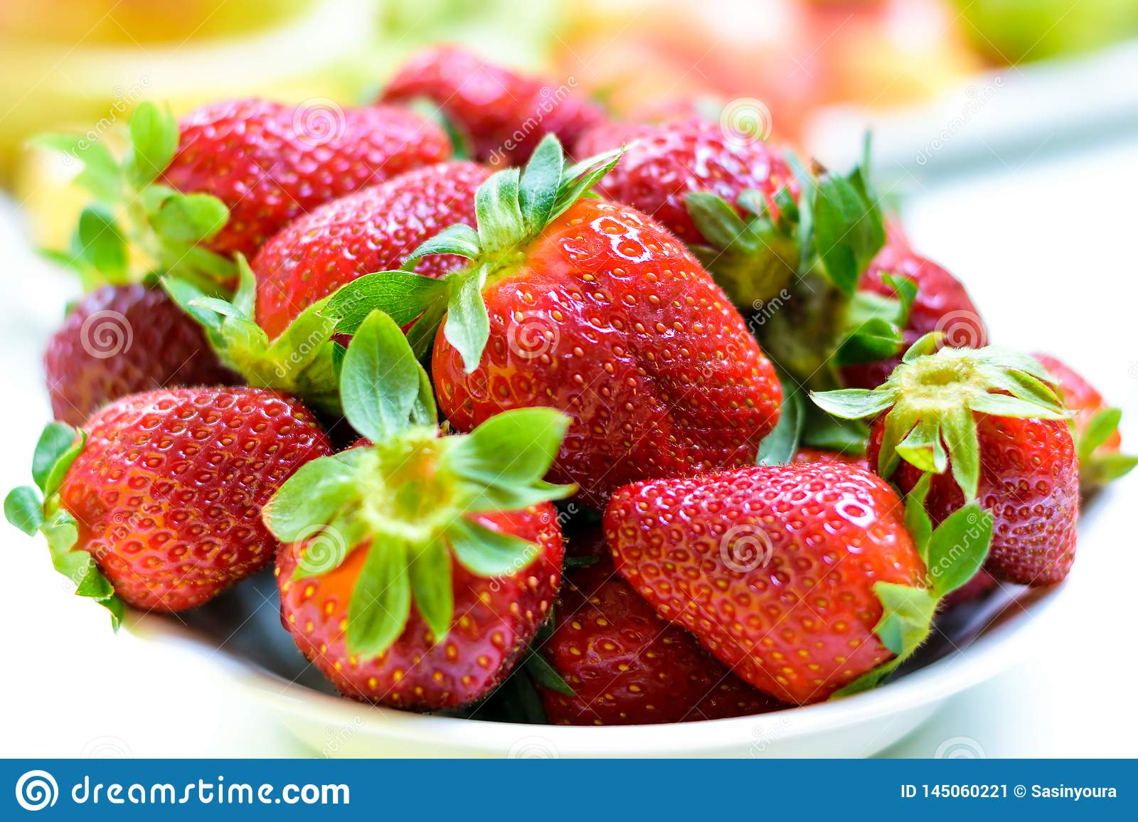 Beautiful red strawberry. Heap of fresh strawberries in ceramic bowl on a rustic white background on the table.
