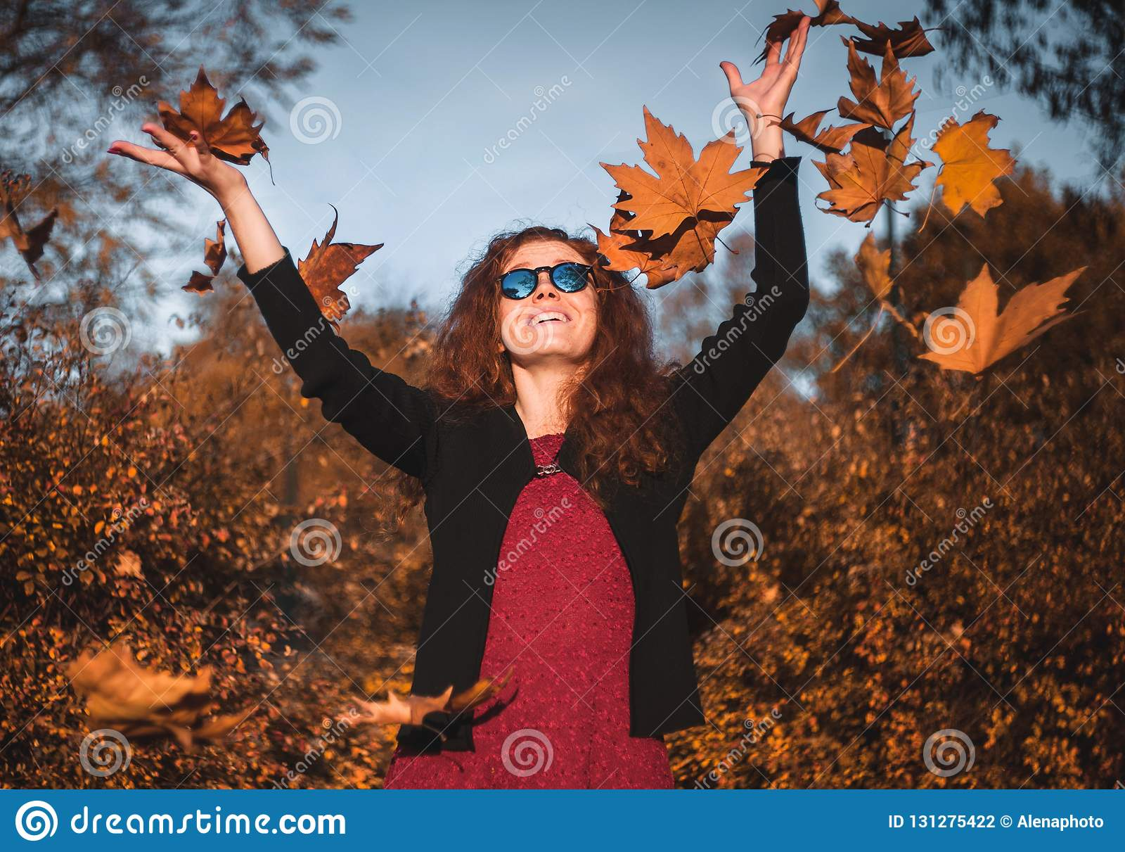 Beautiful redhaired girl with a falling leaves.