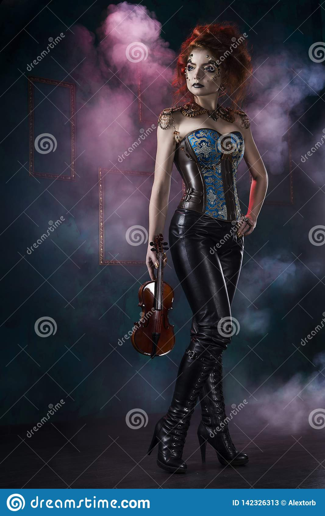 Beautiful redhead cosplayer girl wearing a steampunk corset and leather pants with a big breast holds violin in her hand in