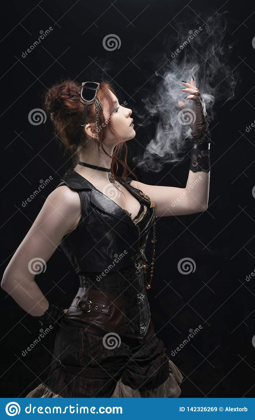 A beautiful redhead cosplayer girl wearing a Victorian-style steampunk costume with big breasts in a deep neckline holds her hand