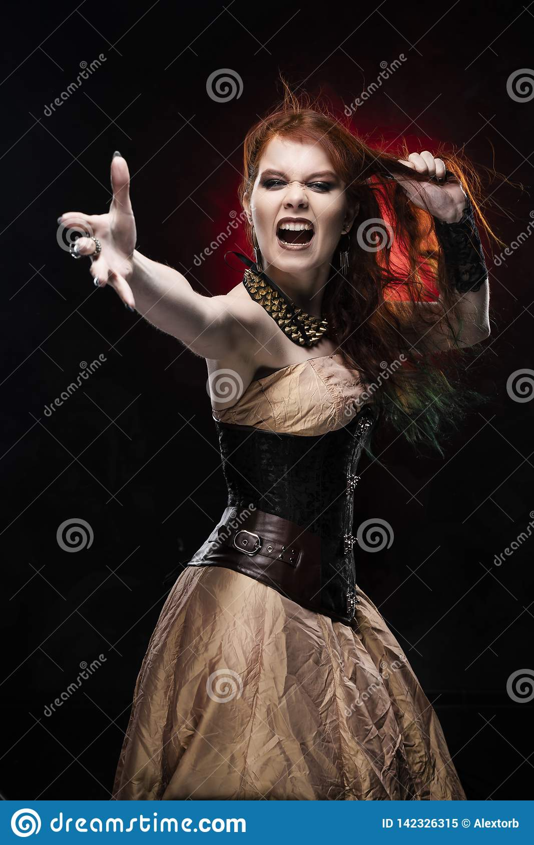 Beautiful redhead cosplayer girl wearing Victorian-style steampunk dress screams, pulls her hair by her hand and outstretching her