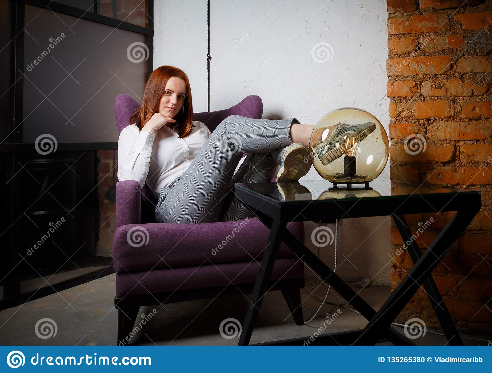 Beautiful refined girl with long red hair sitting relaxed in leather brown chair. Bright warm colors, lifestyle and loft interior