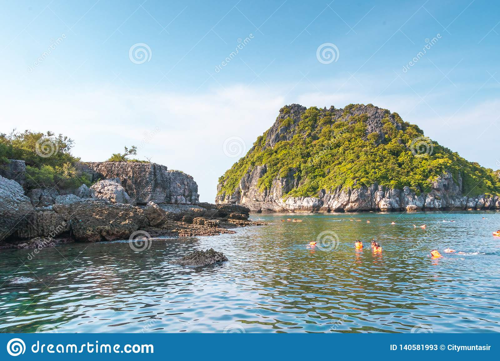 Beautiful Rocks with vegetation and Swimmers are swimming in the sea underneath blue sky