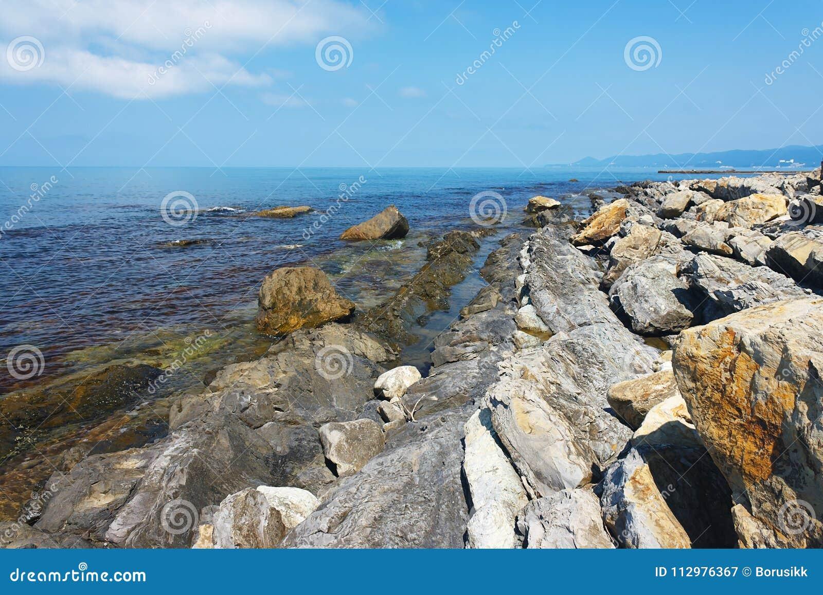 Beautiful rocky coast of the sea under blue sky