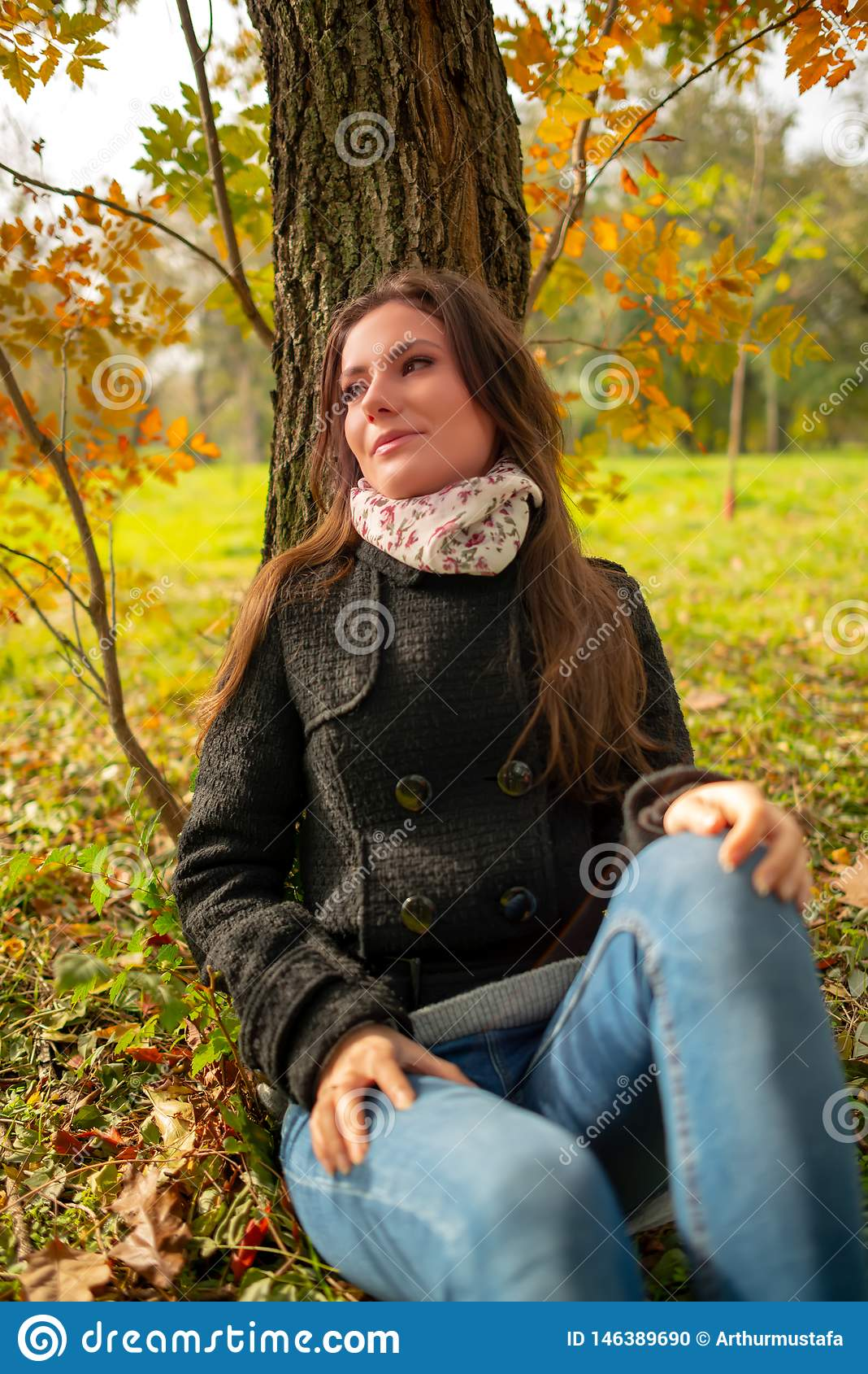 Beautiful romantic girl in a park autumn scenery, sitting down and leaning against a tree, enjoying the warm sunny day