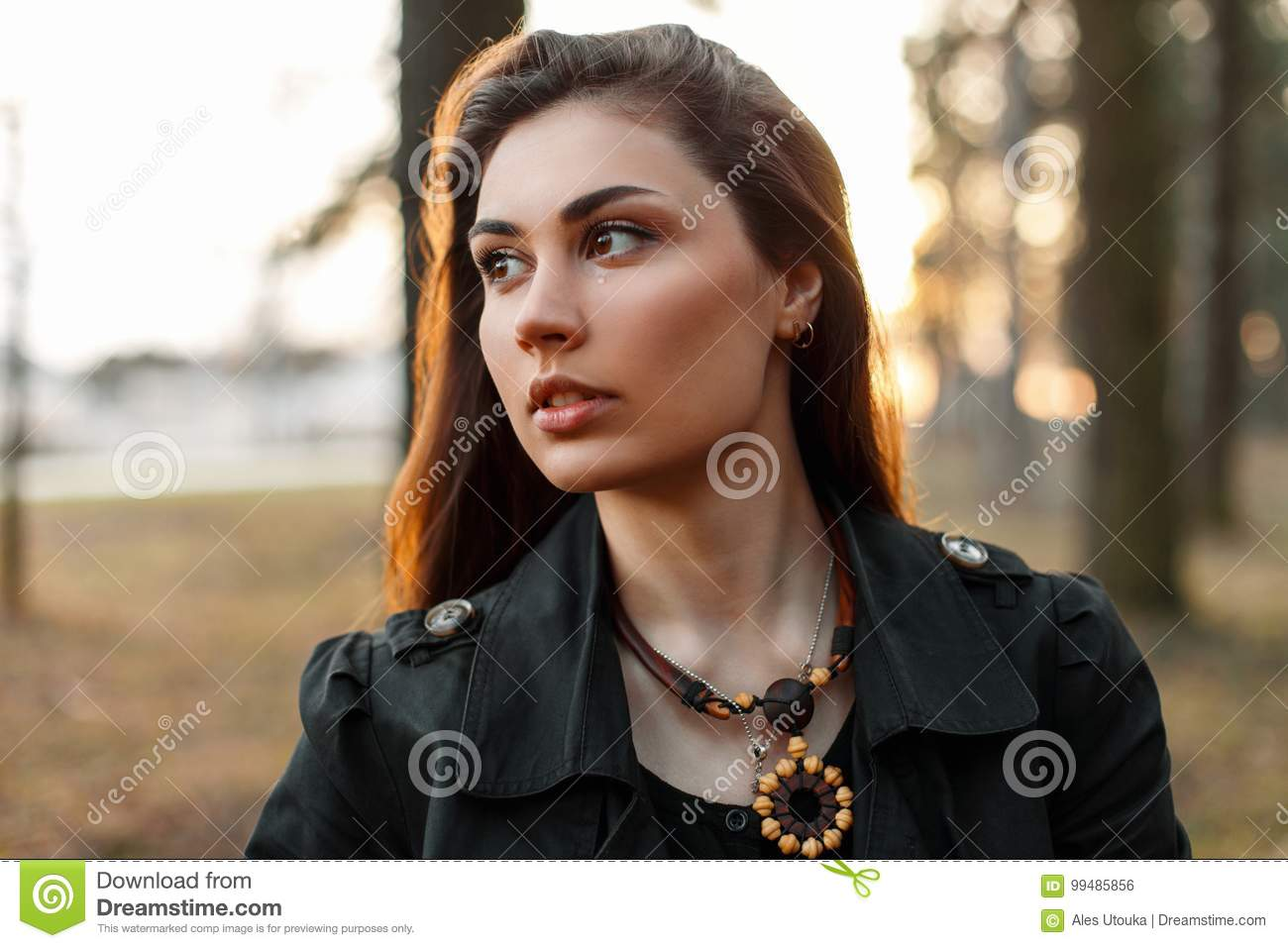 Beautiful sad girl with a tear in the park at sunset