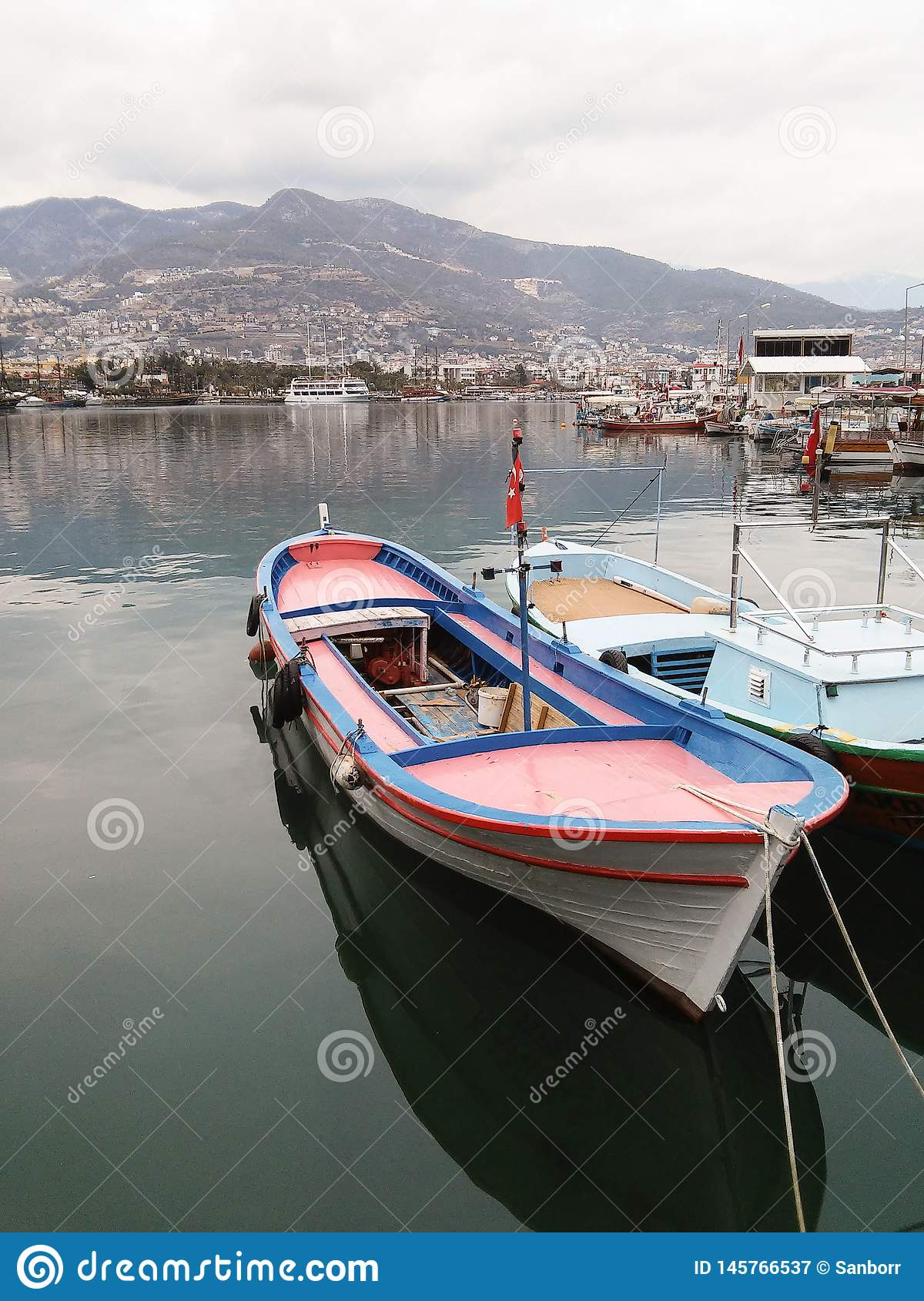 Beautiful scenery. Small boats stand in the port, in the background of the city and the mountains. Turkey