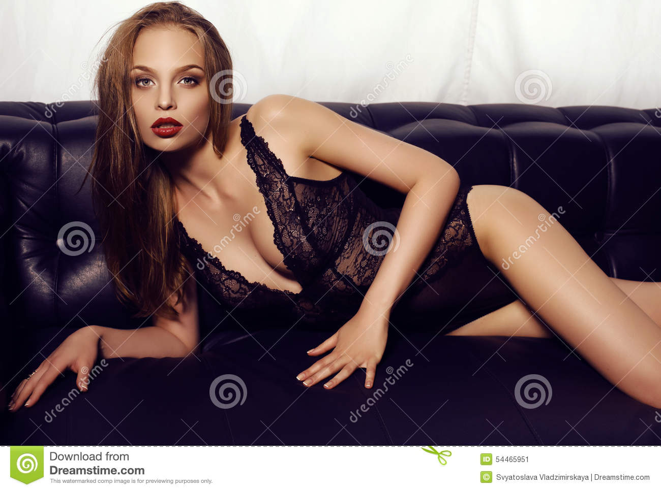 db6db4b15a0e Fashion studio photo of beautiful sensual girl with long dark hair wearing  luxurious lace lingerie, lying on black leather divan