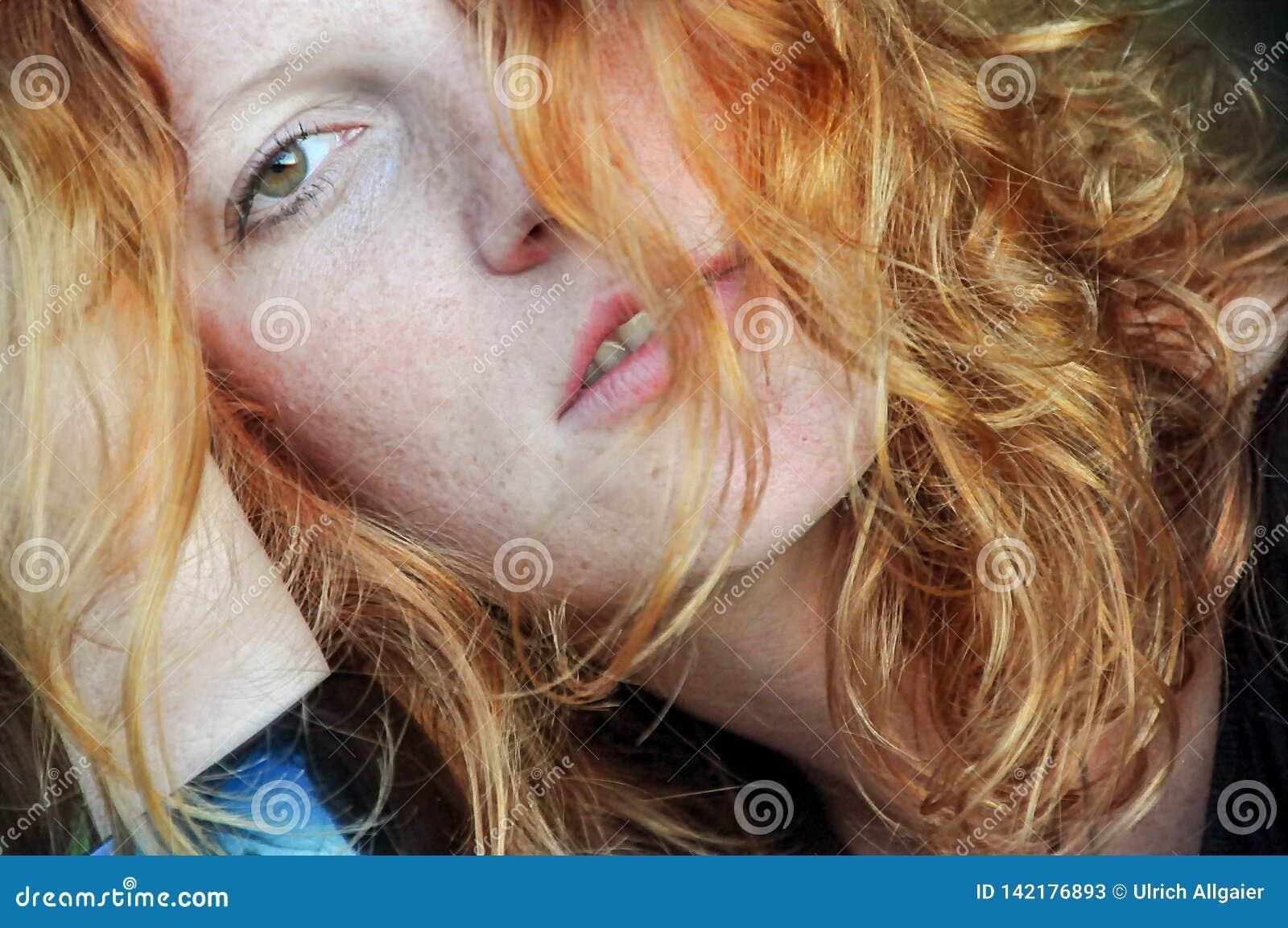 Beautiful sensual portrait in closeup of a thoughtful young redhead wistful