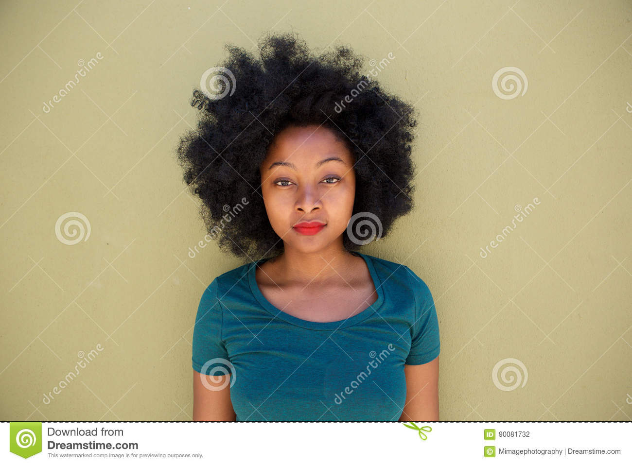 Beautiful serious young black woman standing by wall