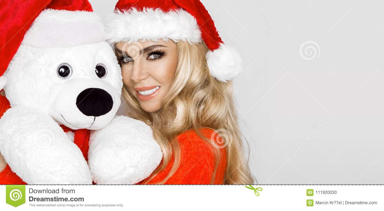 Beautiful blonde female model dressed in a Santa Claus hat embraces a white teddy bear in a red cap Christm