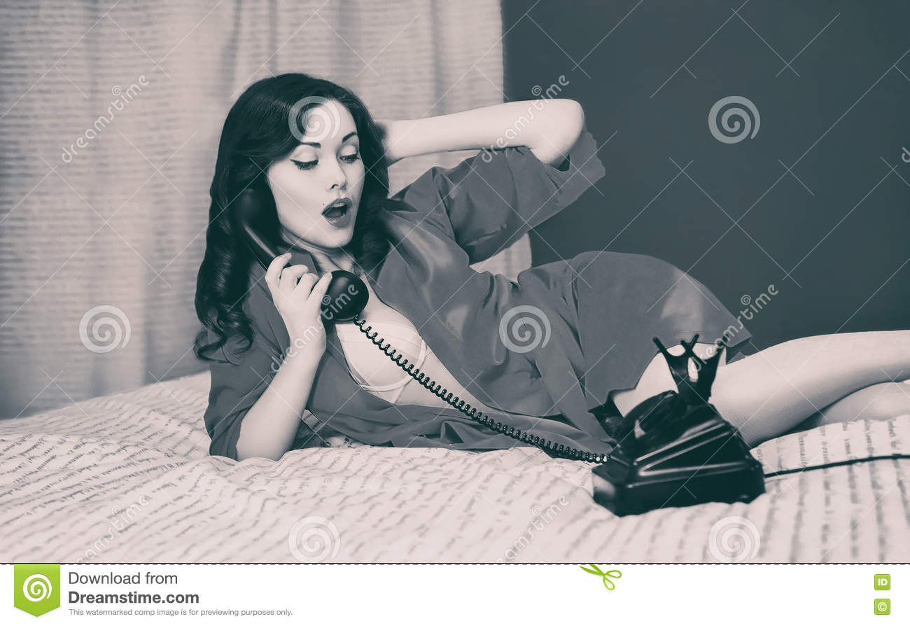Beautiful brunette woman lying on bed talking on the vintage telephone retro black and white film photo