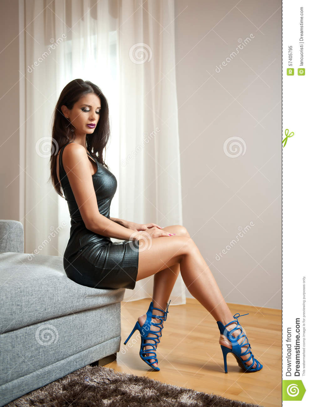 fc4d58c414 Beautiful brunette young woman wearing black leather short dress sitting on  bed. Fashionable female with