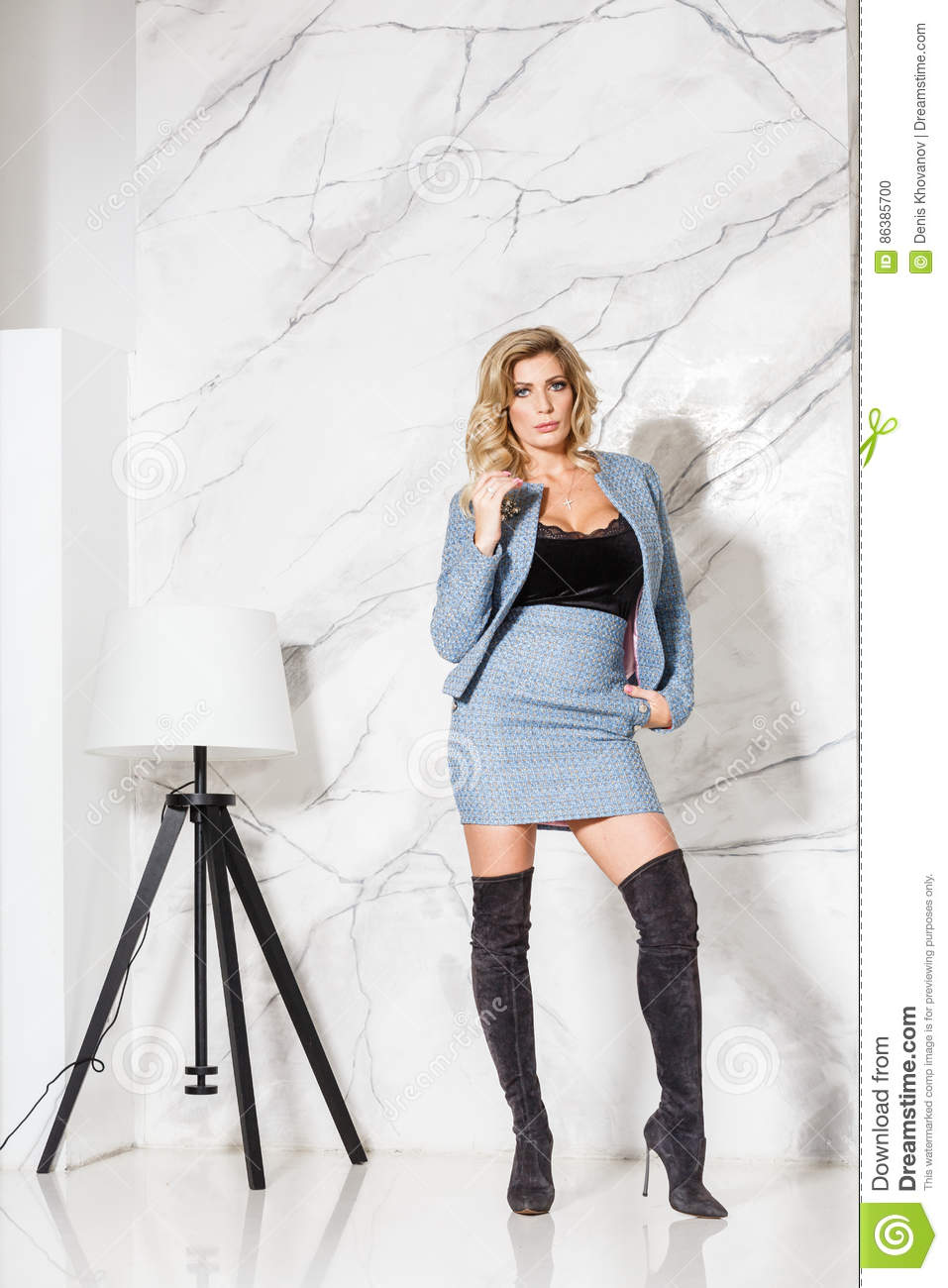 Beautiful blonde in business skirt and jacket posing on a marble background