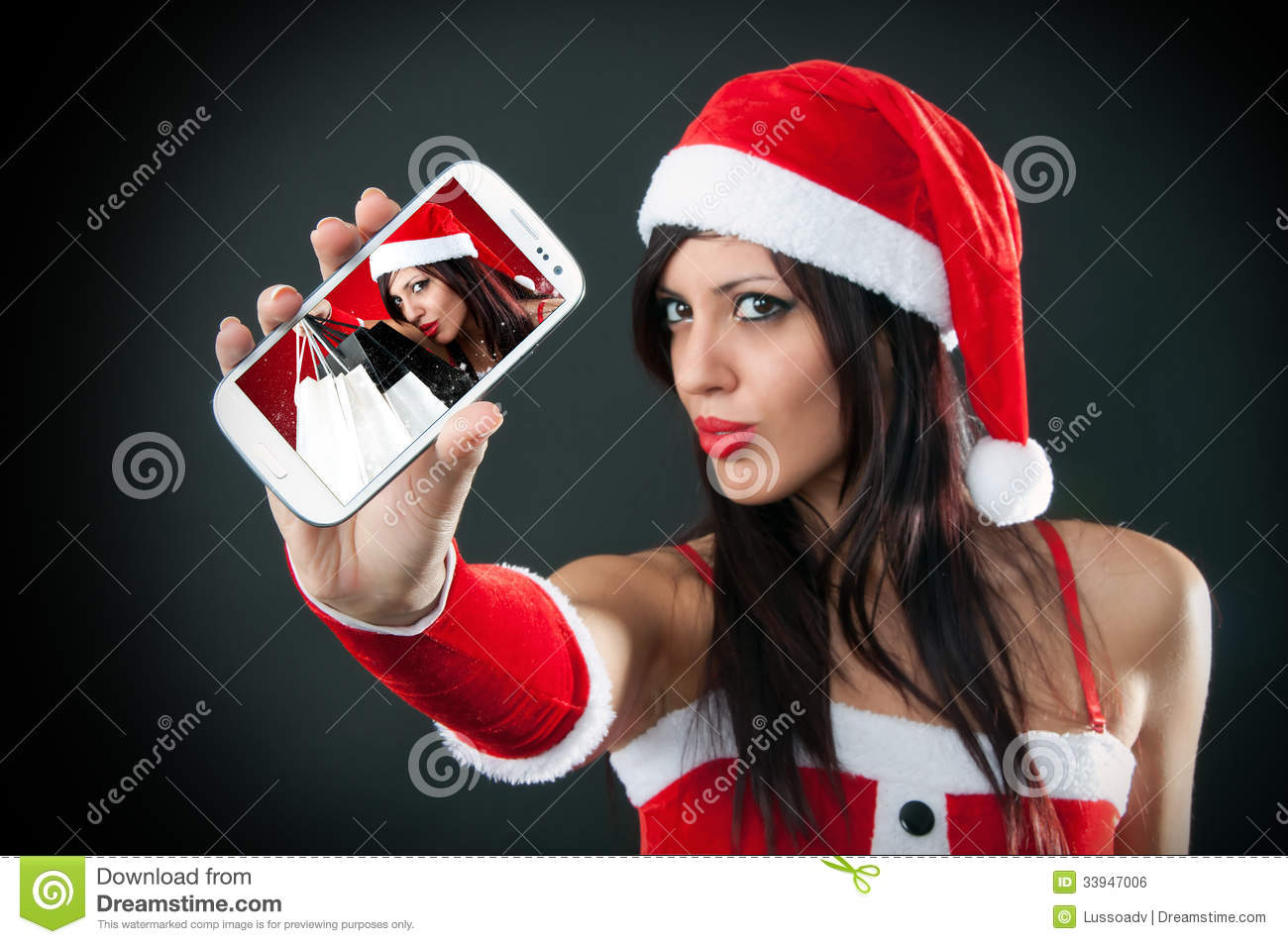 beautiful sexy girl wearing santa claus clothes with smart phone